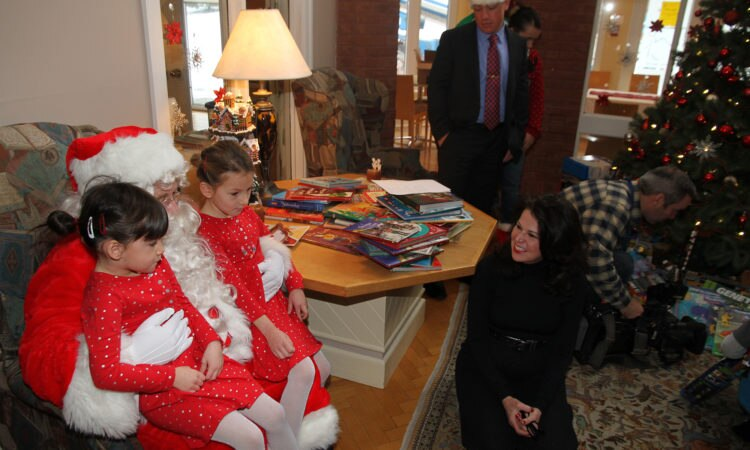 Mrs. Vicki Heyman and Santa help the Marines bring Toys for Tots to Ottawa's Ronald McDonald House.