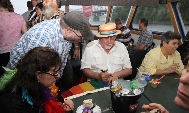 Rainbow Flag creator Gilbert Baker signs a flag on the Ottawa Pride Boat Cruise.